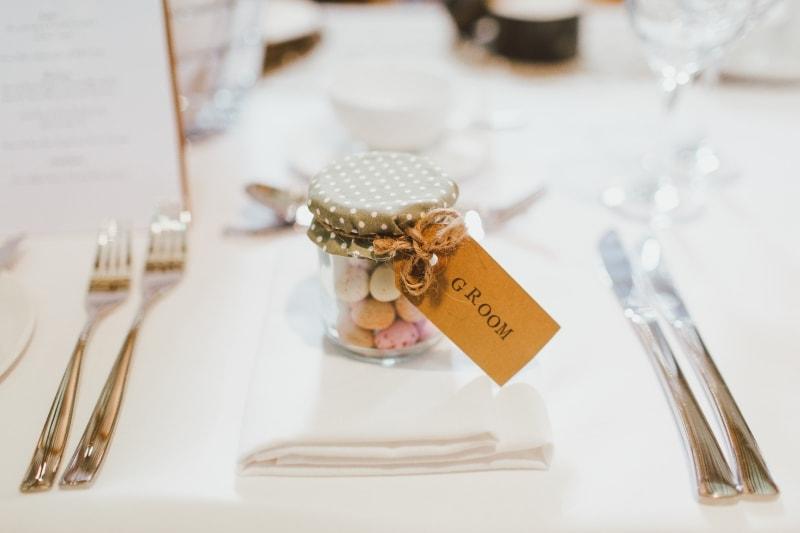 Na środku zdjęcia na nakrytym stole znajduje się prezent w słoiczku.